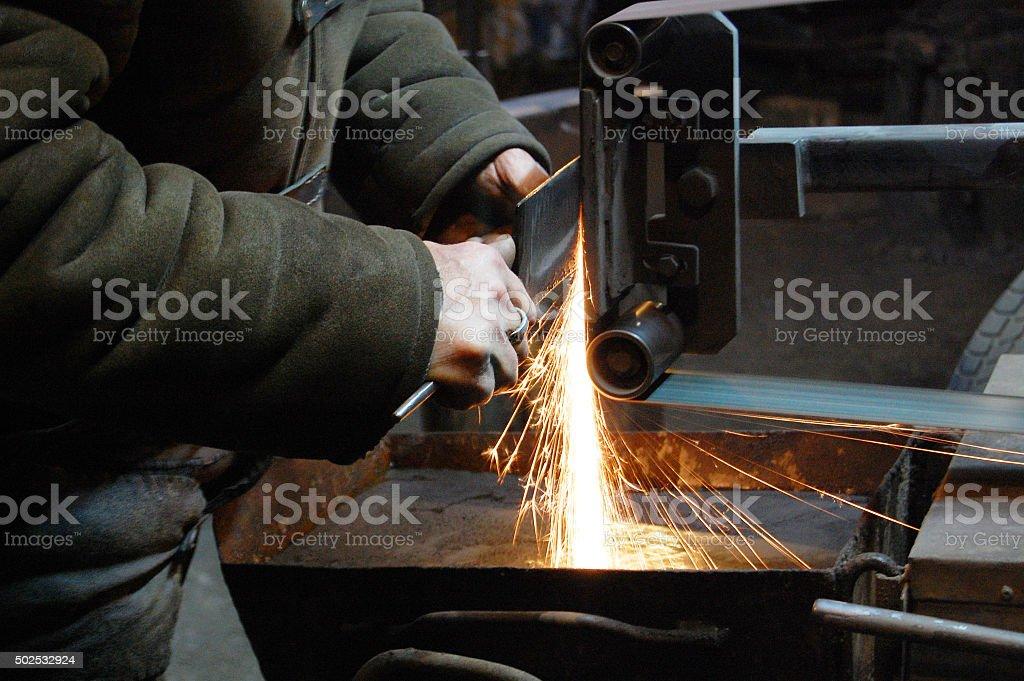 Blacksmith turning a knife stock photo