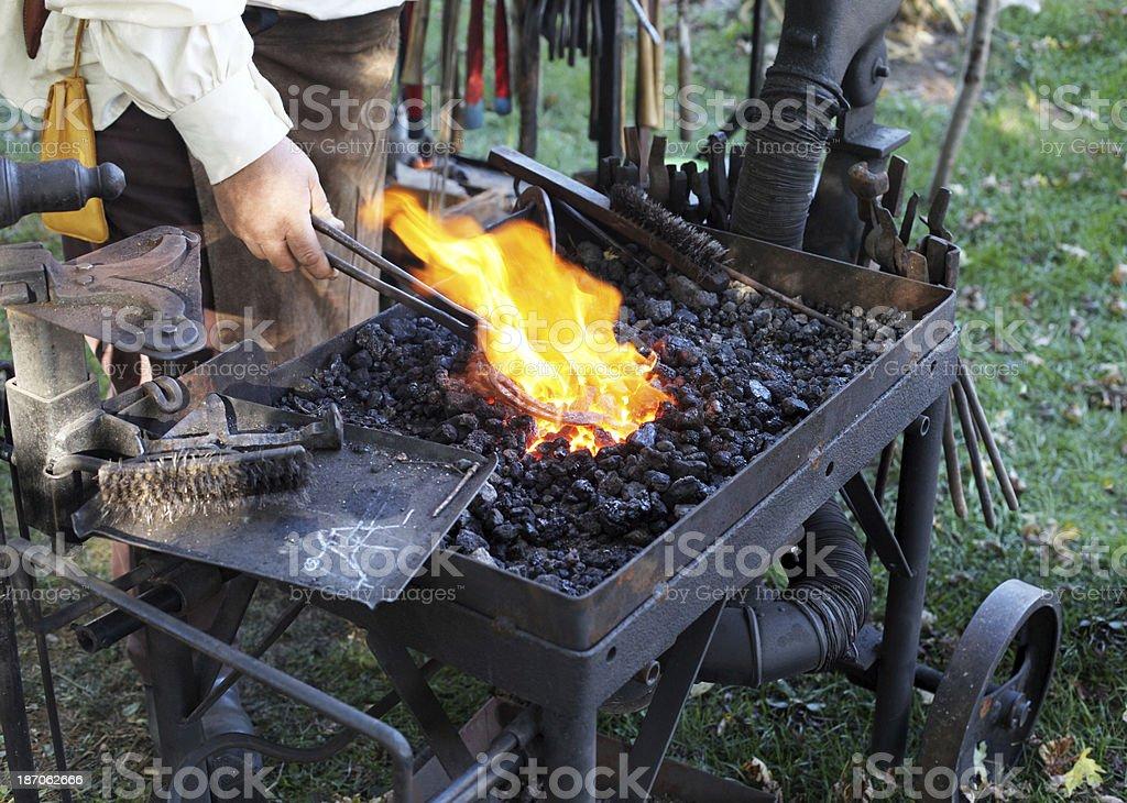 Blacksmith uses tongs to hold horseshoe in fire. royalty-free stock photo