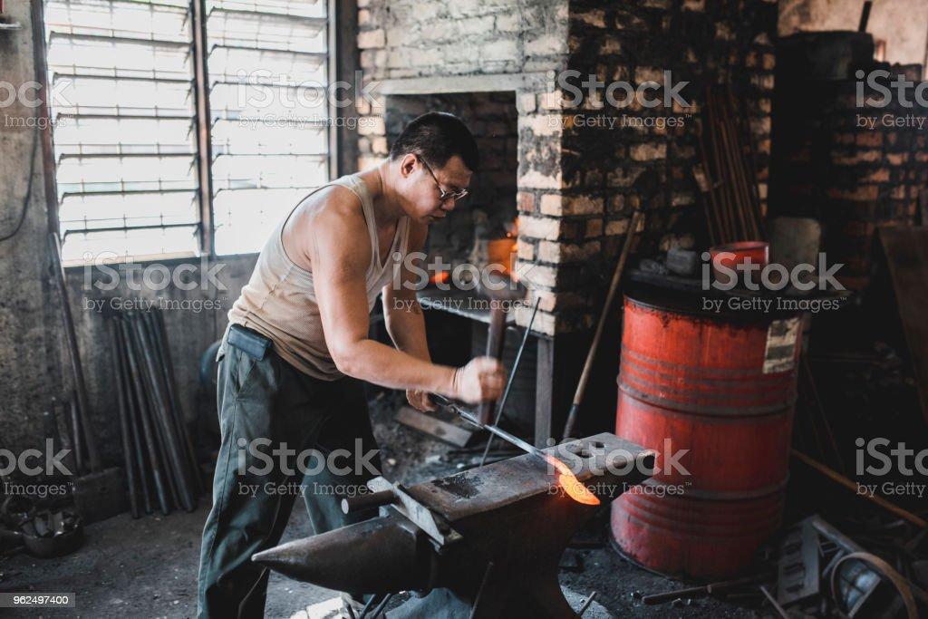 Ferreiro trabalhando em sua oficina de metal - Foto de stock de 40-49 anos royalty-free