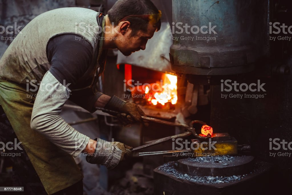 blacksmith working in the forge stock photo