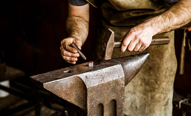 blacksmith working on a anvil stock photo