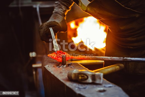 istock blacksmith working on an anvil 865992922