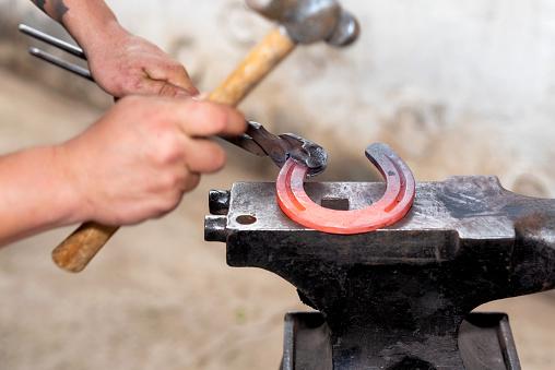547224670 istock photo Blacksmith working on the anvil, making a horseshoe. 1132747318