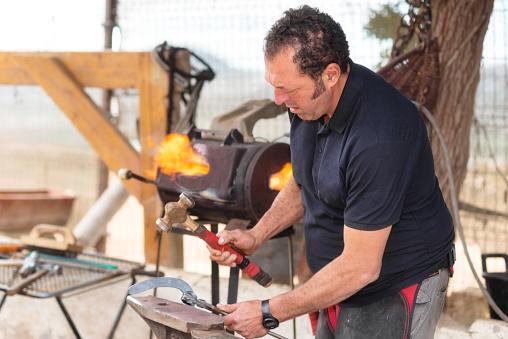 547224670 istock photo Blacksmith working on the anvil, making a horseshoe. 1132747552
