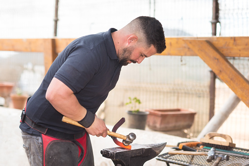 547224670 istock photo Blacksmith working on the anvil, making a horseshoe. 1132750599