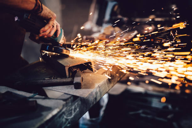Blacksmith working with power tools and metals in workshop Mechanic cutting metal with angle grinder with sparks flying off while working in workshop garage grinding stock pictures, royalty-free photos & images