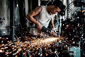 Young Asian blacksmith working with power tools in workshop. Blacksmith's workshop in Malaysia.