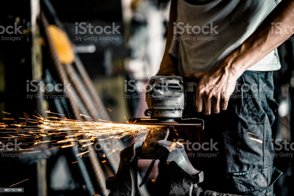 Blacksmith working with power tools in workshop - Foto stock royalty-free di Abilità