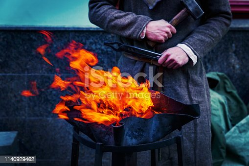 547224670istockphoto Blacksmith workshop on the street. People in traditional clothses forge metal 1140929462