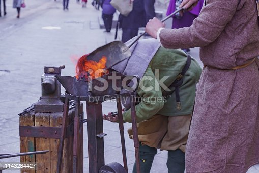 547224670istockphoto Blacksmith workshop on the street. People in traditional clothses forge metal 1143284427