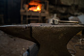 istock A blacksmith's hammer lies on an anvil against the background of a burning forge 1284887337