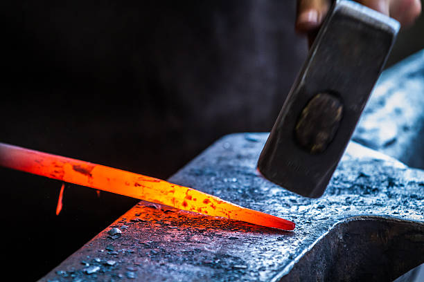 Blacksmith's hammer working a heated metal rod on an anvil stock photo