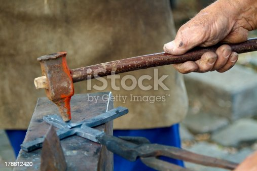 istock Blacksmiths hand and hammer 178612420