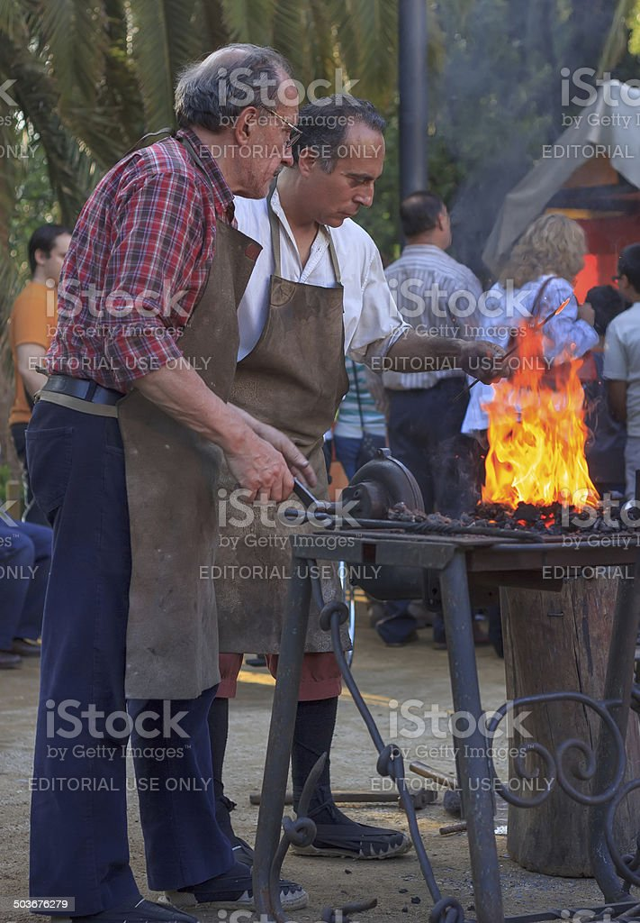 Blacksmiths working on metal  at forge in the moder stock photo