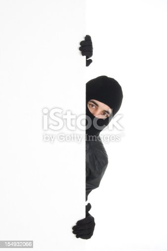 istock Black-wearing thief spying out the white wall/background 154932066