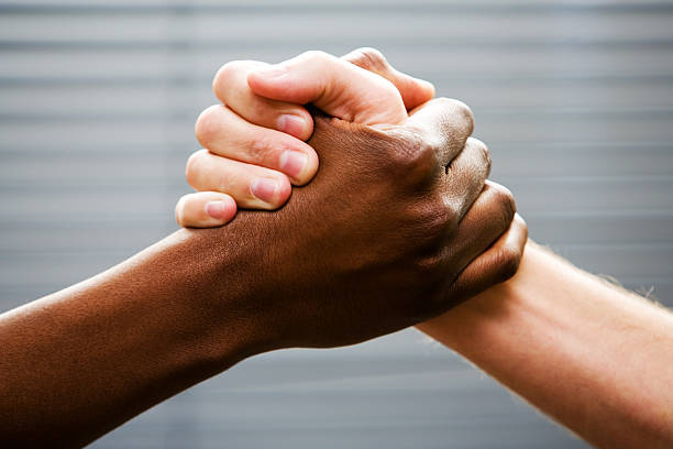 Black-white arm wrestling Black and white hands clasped, with blurred office blinds as backdrop.This is an African gesture of greeting and friendship but it will double for arm-wrestling, symbolizing competition or rivalry. Camera: Canon 5D.More in this series: brother stock pictures, royalty-free photos & images