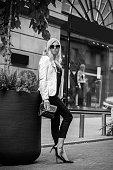 Black-white image of beautiful young girl. Beautiful young blond girl posing on street. Fashion, beauty.