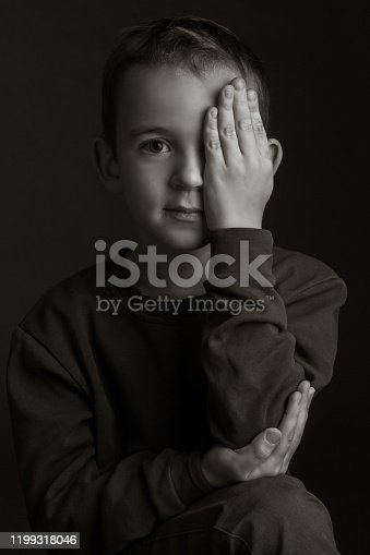 black-and-white portrait of a dark-haired boy covering his eye with his hand on a black background
