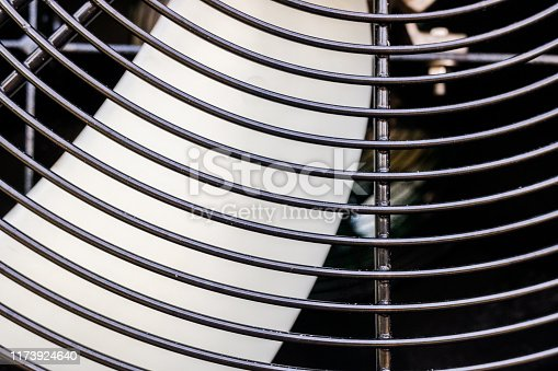 istock Blades of an industrial fan protected by a grid. 1173924640