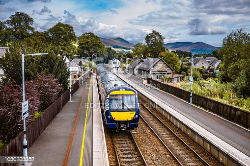 Train departing Blair Atholl railway station in the Scottish Highlands. The view is southwards and the three car diesel train is travelling from Inverness to Perth. The line is single track with twin sections at railroad stations.