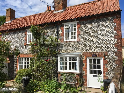 Blakeney, United Kingdom - July 15, 2016: Traditional flint cottages in Blakeney village.  The cottages and narrow lanes give Blakeney a timeless quality that is so loved by its many visitors throughout the year.