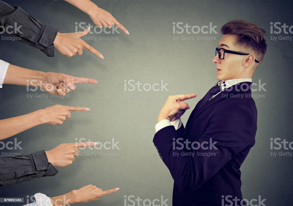 Blaming you. Anxious man judged by different people pointing fingers at him. Negative human emotions feeling stock photo