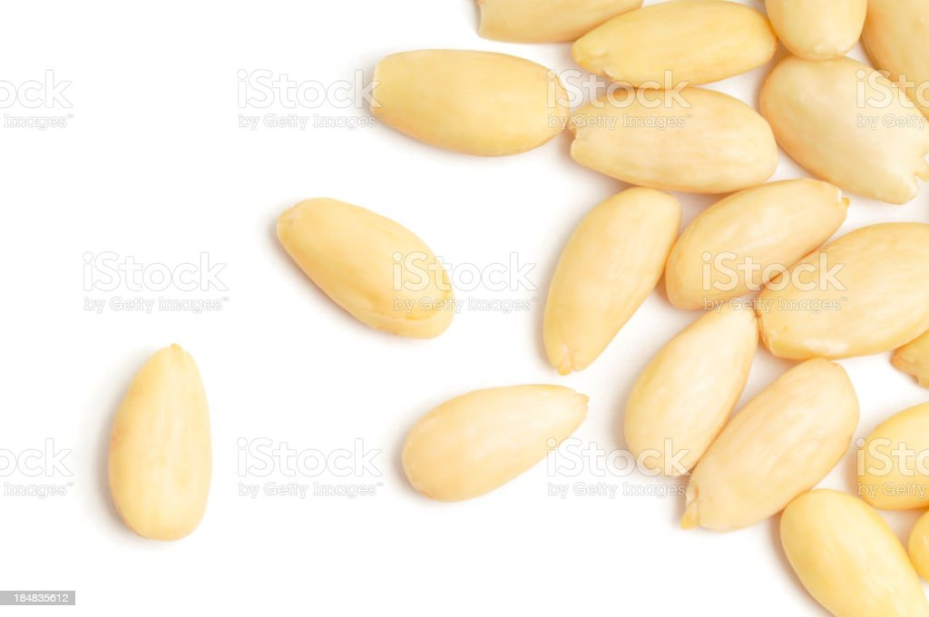 Blanched Almonds Scattered Blanched Almonds scatttered across a white background. Almond Stock Photo