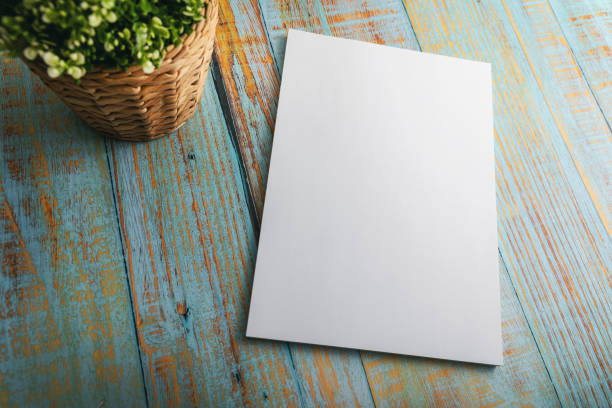blank A4 brochure mockup on blue wooden background stock photo