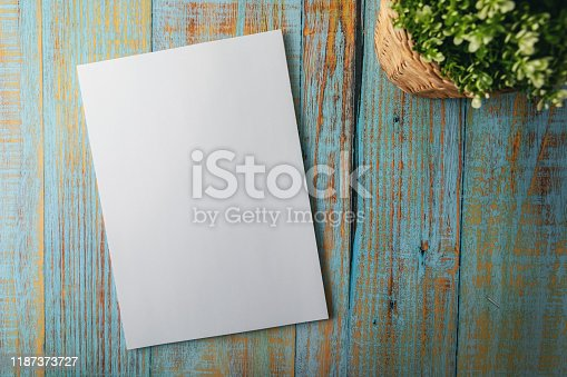 blank A4 brochure mockup on blue wooden background. top view