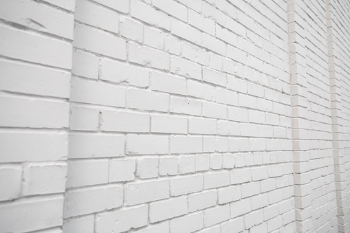 Blank ad space on a white brick wall in the street outside