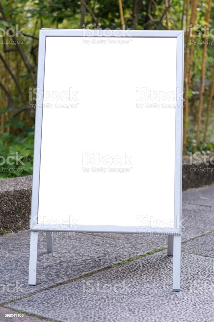 Blank ad space sign infront of trees in a park on the ground