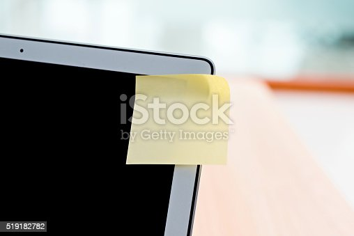 Blank adhesive note on laptop.