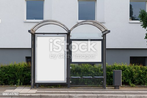 1036904778 istock photo Blank advertisement mock up in a bus stop 956143762