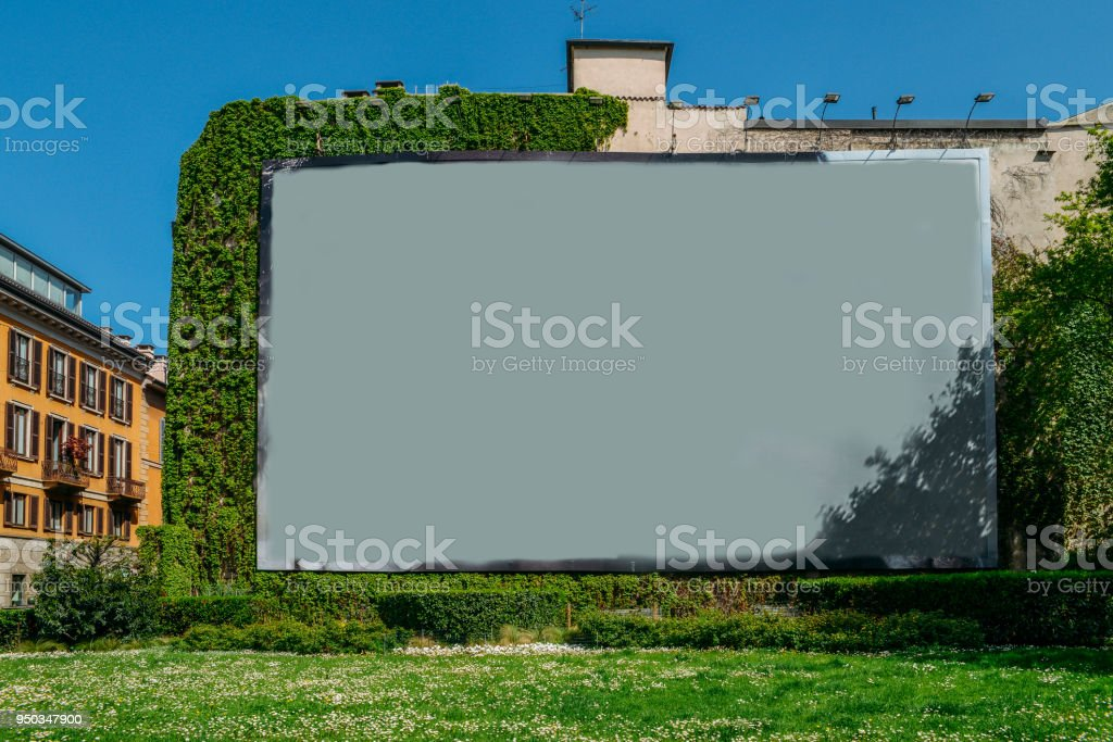 Blank advertisement space on wall next to grass and vines. - foto stock