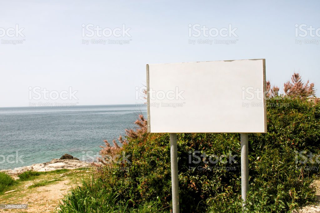 Blank advertising billboard display and table, sea in background....