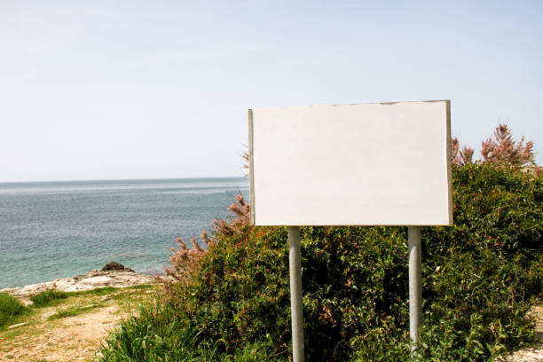 Blank advertising billboard display and table, sea in background. Advertising agencies. Billboard with copy space for text message or content, outdoor advertising mock up, public information board. stock photo