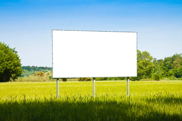 A blank advertising billboard in a grass field - image with copy space stock photo