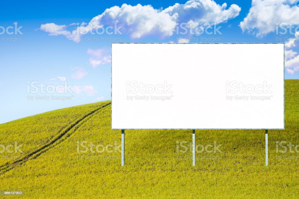 Blank advertising billboard in a green field - image with copy space - Royalty-free Advertisement Stock Photo