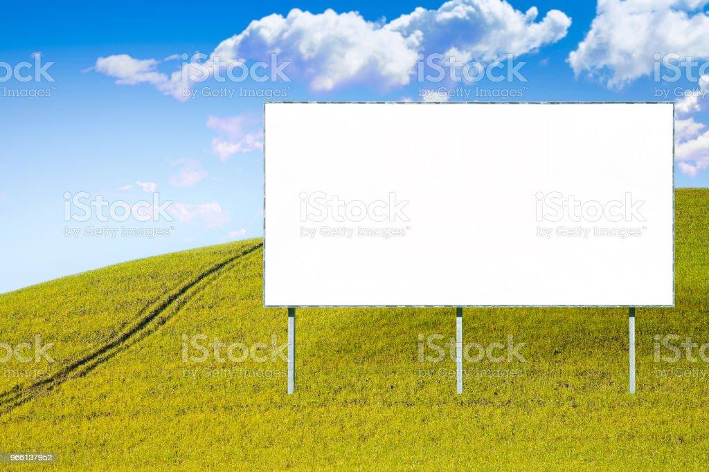 Tom reklam skylt i ett grönt fält - bild med kopia utrymme - Royaltyfri Affischtavla Bildbanksbilder
