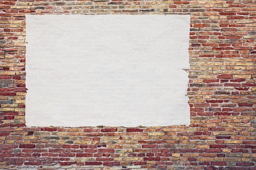 istock blank advertising poster glued to the brick wall 1093898170