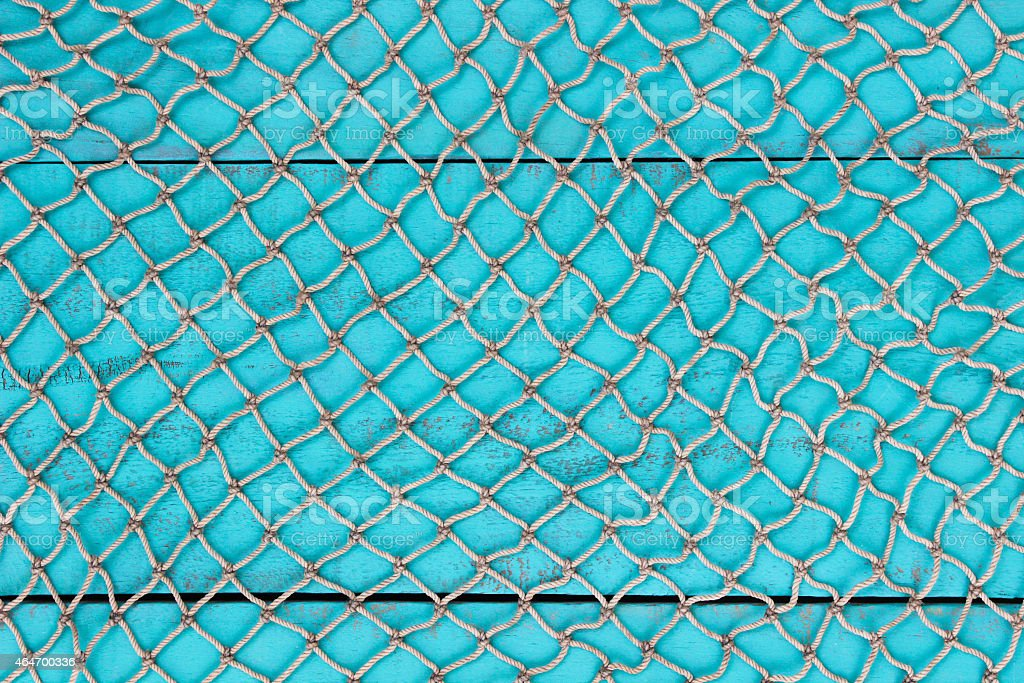Blank antique teal blue wooden sign and fish netting background stock photo