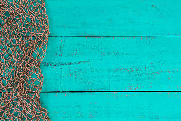 Blank antique teal blue wooden sign with fish net border Blank antique teal blue aged wooden sign with fish net border fishing net stock pictures, royalty-free photos & images