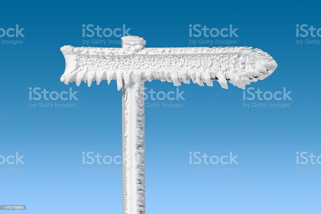 blank arrow sign covered by frost stock photo