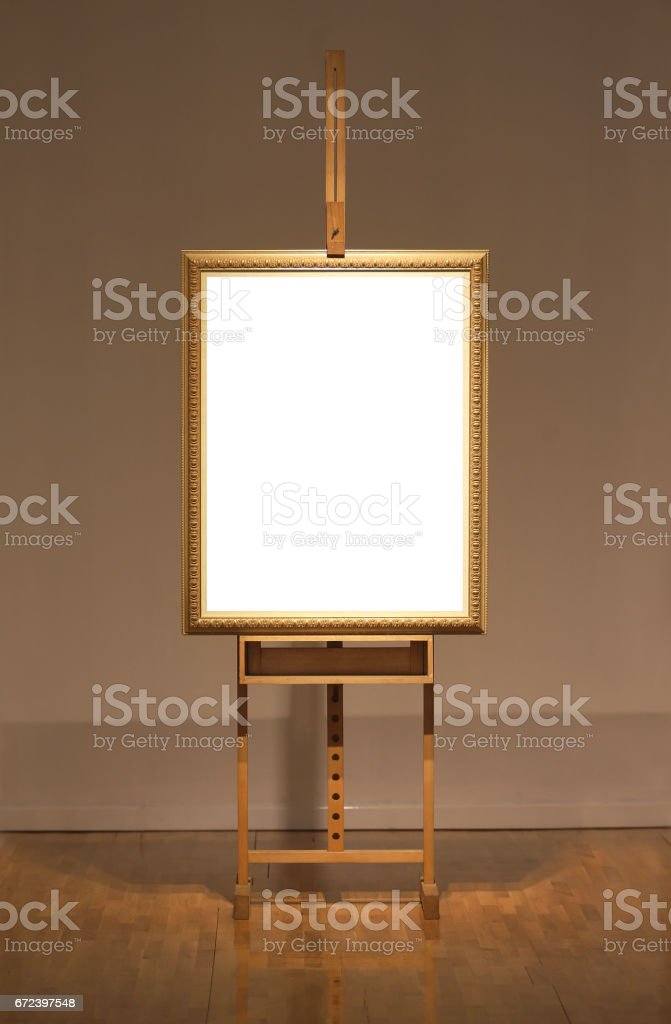 Blank art frame on wooden easel in museum stock photo