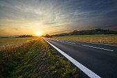 Blank asphalt road running towards sunset in rural countryside