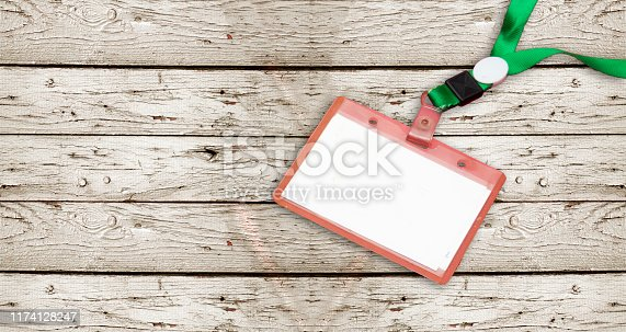 istock Blank badge mockup isolated on wooden background. Plain empty name tag mock up hanging on neck with string. Name Tag, Corporate design. 1174128247