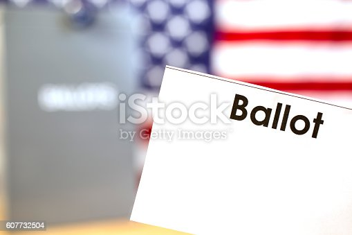 1001757106 istock photo Blank ballot with ballot box and USA flag background. 607732504