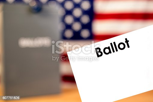 1001757106 istock photo Blank ballot with ballot box and USA flag background. 607751826