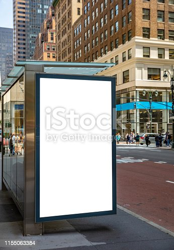 1036904778 istock photo Blank billboard at bus stop for advertising, New York city buildings and street background 1155063384