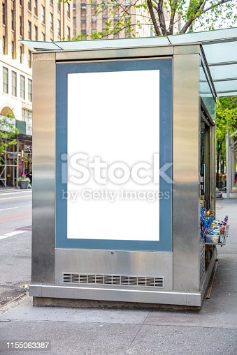 1036904778 istock photo Blank billboard at bus stop for advertising, New York city buildings and street background 1155063387